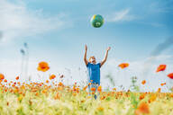 Boy catching globe while standing in poppy field against blue sky on sunny day - MJF02398