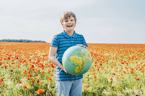 Portrait of smiling boy holding globe in poppy field against sky on sunny day - MJ02401
