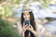 Smiling young woman wearing a straw hat and using her smartphone outside - SGF02403