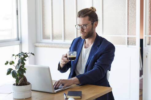 Businessman with laptop and cup of coffee at table - JSRF00457