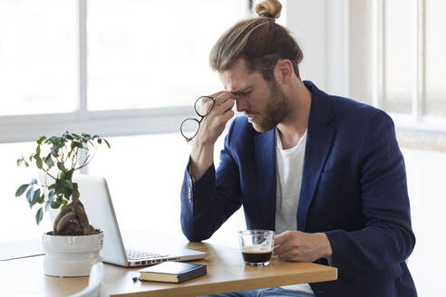 Tired businessman sitting at table in office - JSRF00460