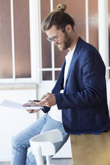 Smiling young businessman using smartphone in office - JSRF00466