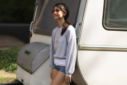 Young woman with sunglasses leaning on camper - TWOF00011