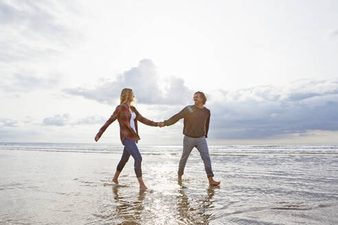 Couple walking and holding hands in ocean surf - JUIF02418