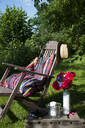 Cushion made of patchwork rug on deckchair in the garden - GISF00434