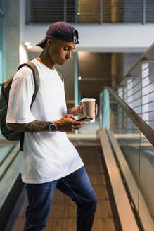 Young man with backpack and coffee to go standing on escalator looking at cell phone - MGIF00543
