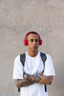 Portrait of tattooed young man listening music with wireless red headphones - MGIF00552