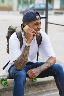Portrait of tattooed young man on the phone sitting on his skateboard outdoors - MGIF00576