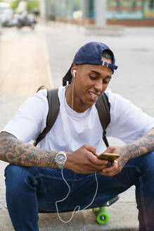 Portrait of tattooed young man sitting on skateboard listening music with smartphone and earphones - MGIF00579