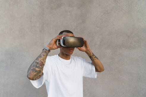 Tattooed young man using Virtual Reality Glasses looking up - MGIF00582