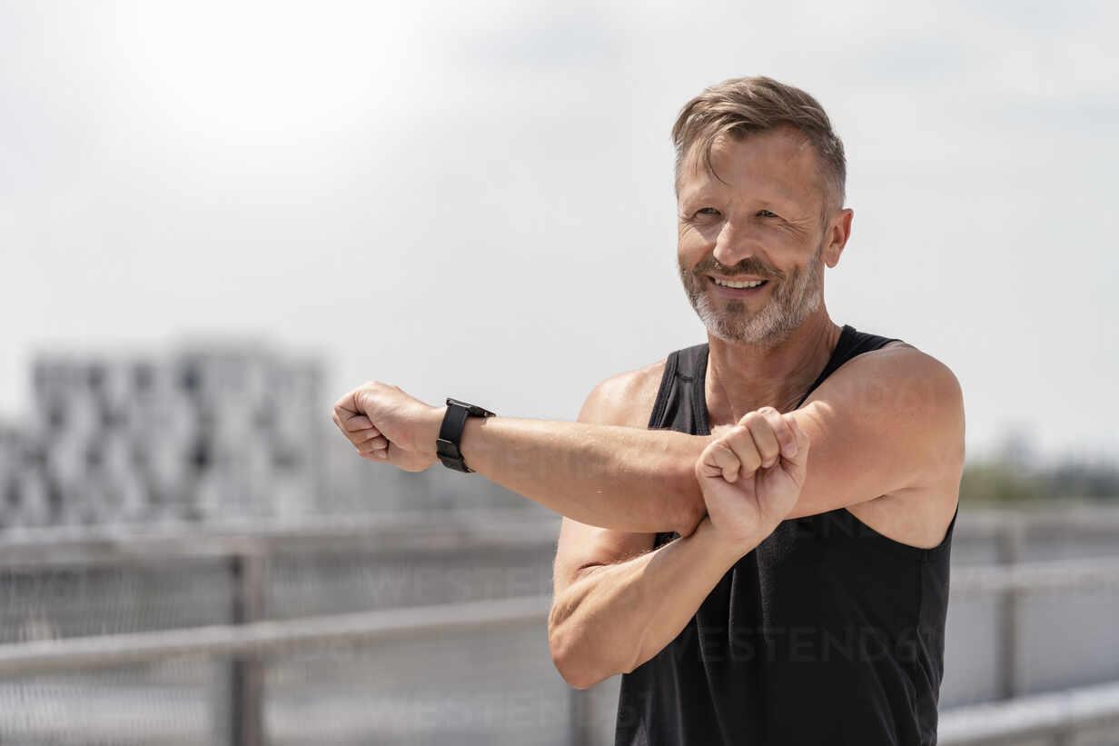 Sporty man stretching outside - DIGF07485 - Daniel Ingold/Westend61