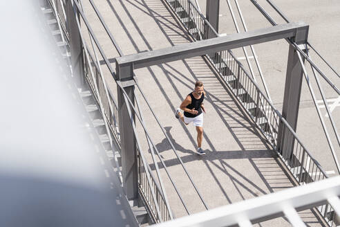 Sporty man jogging over bridge - DIGF07488