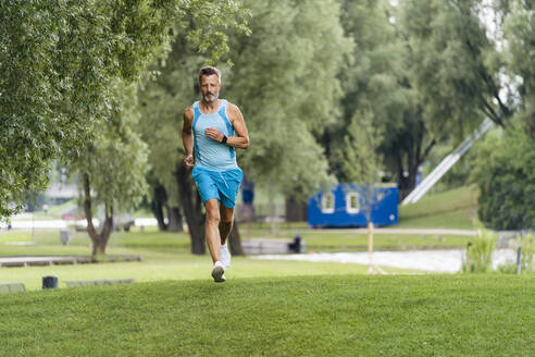 Sporty man jogging in a park - DIGF07500