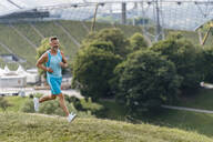 Sporty man jogging in a park - DIGF07503