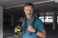 Sporty man with drinking bottle after workout - DIGF07530