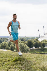 Sporty man jogging in a park - DIGF07545