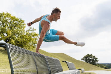 Sporty man jumping over a bench in a park - DIGF07551