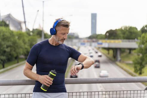 Sporty man standing on a bridge, wearing headphones and checking his smartwatch - DIGF07554