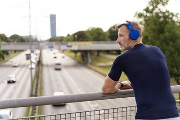 Sporty man standing on a bridge wearing headphones - DIGF07557
