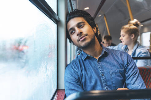 Portrait of daydreaming young man travelling by bus, London, UK - WPEF01587