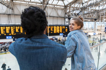 Happy young woman waiting with her friend at train station, London, UK - WPEF01590