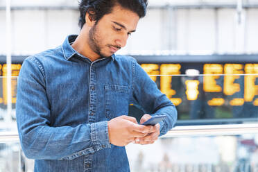 Young man wearing denim shirt using smartphone at train station, London, UK - WPEF01593