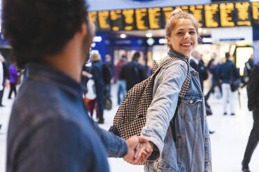 Portrait of happy young woman hand in hand with his boyfriend at train station - WPEF01596