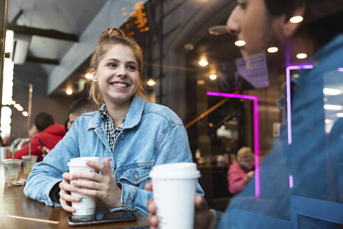 Portrait of smiling young woman in a coffee shop looking at young man - WPEF01608