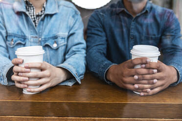 Hands holding disposable cups in a coffee shop, partial view - WPEF01611