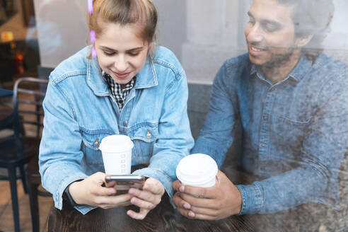 Young woman using smartphone in a coffee shop while her boyfriend watching her - WPEF01617