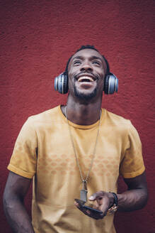 Portrait of happy man with headphones and smartphone looking up - OCMF00480
