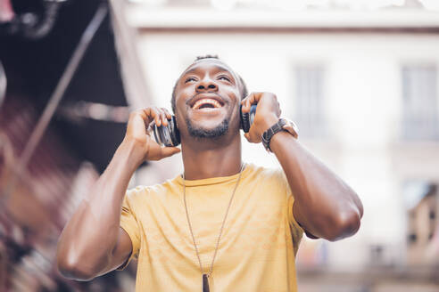Portrait of happy man listening music with headphones looking up - OCMF00489