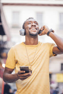 Portrait of happy man listening music with headphones and smartphone - OCMF00492
