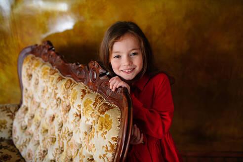 Portrait of smiling little girl wearing red dress - OGF00076