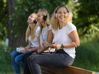 Three young women listening music with headphones and smartphones on a backrest of a bench - STSF02126