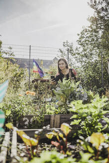 Young woman taking pictures with smartphone in urban garden - VGPF00050
