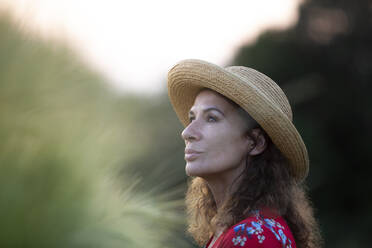 Portrait of woman wearing straw hat in nature - FLLF00247