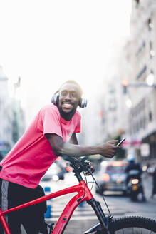 Happy young man with e bike and smartphone in the city - OCMF00497