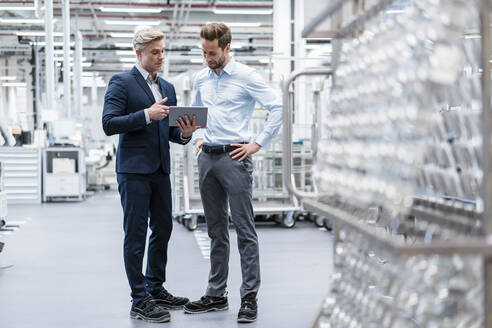 Two businessmen with tablet talking in a modern factory - DIGF07560