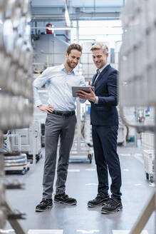 Two businessmen with tablet talking in a modern factory - DIGF07563