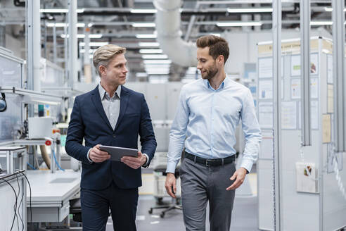 Two businessmen with tablet talking in a modern factory - DIGF07569