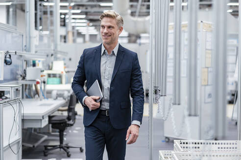 Confident businessman with tablet in a modern factory - DIGF07572