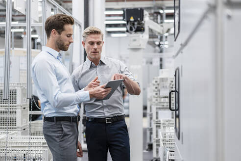 Two businessmen with tablet talking in a modern factory - DIGF07584