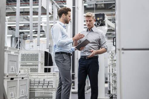 Two businessmen with tablet talking in a modern factory - DIGF07587