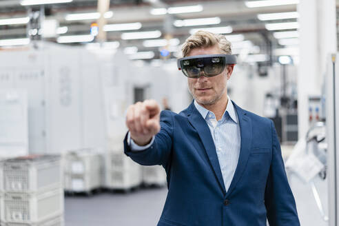 Businessman wearing AR glasses in a modern factory - DIGF07620