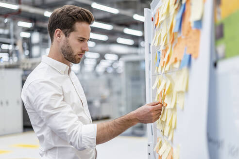 Businessman organizing adhesive notes on a board in a factory - DIGF07644
