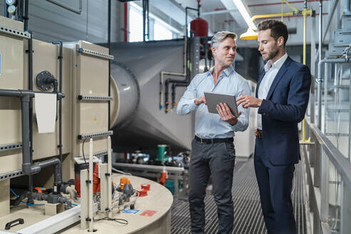 Two businessmen with tablet talking in a modern factory - DIGF07659