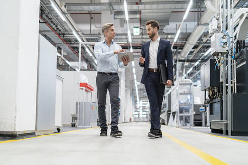 Two businessmen with tablet talking in a modern factory - DIGF07662