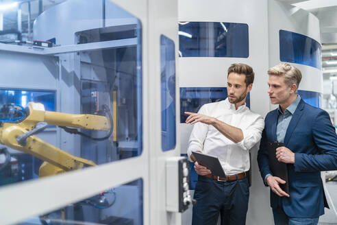Two businessmen talking at robot in a modern factory - DIGF07698