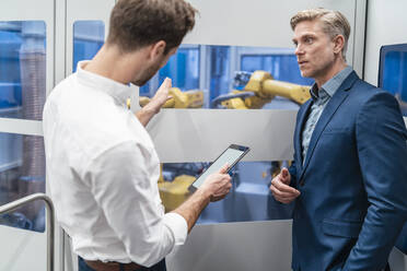 Two businessmen talking at robot in a modern factory - DIGF07701